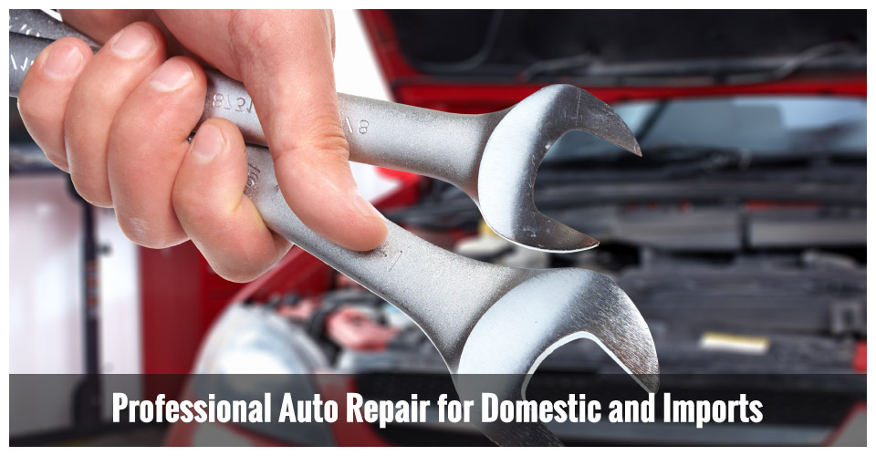 mechanic holding wrenches in front of car | professional auto repair for domestic and imports